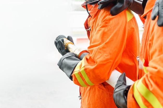Brandbestrijder die brandblusapparaat en water van slang gebruikt voor brandbestrijding