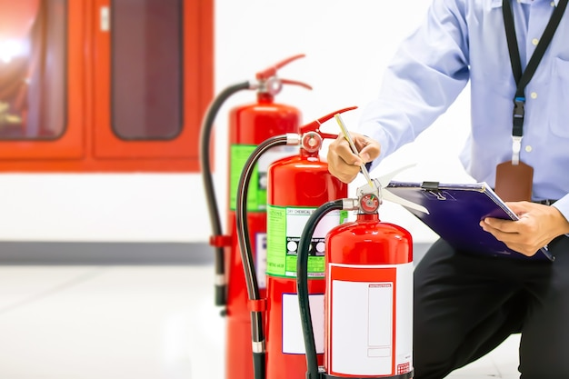 Brandbestrijder die manometerniveau van brandblusapparaat controleert.
