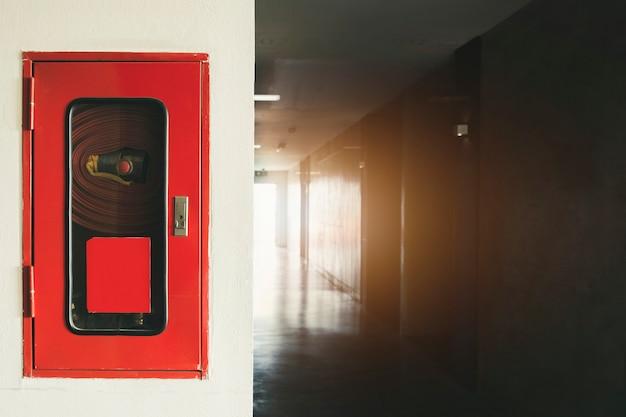 Brandblusapparaat en brandslanghaspel in hotel, brandveiligheidsapparatuur op muurcement