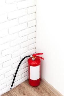 Brandblusser in de buurt van witte muur, klaar voor gebruik