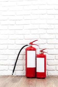 Brandblussers in de buurt van witte muur