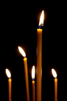Branden in het donker taps toelopende kaarsen. het vuur dat brandt in de duisternis