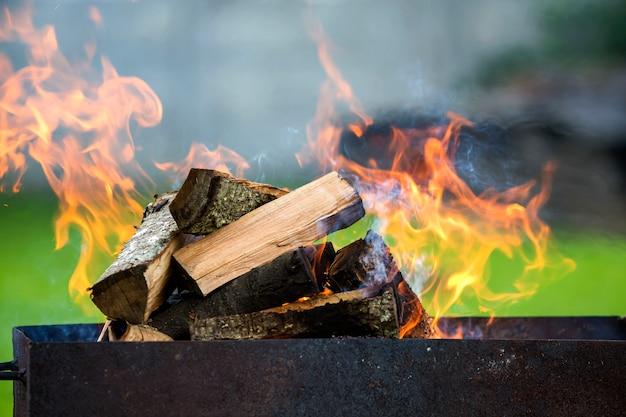 Branden in metalen doos brandhout voor barbecue buiten.