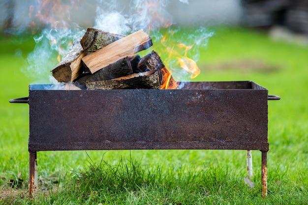 Branden in metalen doos brandhout voor barbecue.