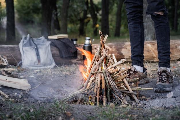 Brandend kampvuur in de buurt van een bos. reizen naar het wilde concept: kampeerplaats met vintage rugzak, thermoskan en mannelijke voeten in trekkingschoenen bij een open haard buitenshuis