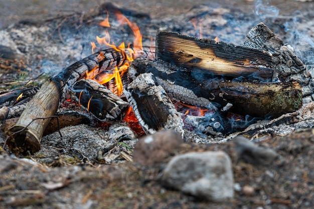 Brandend logboek van hout close-up als abstracte achtergrond, de hete sintels van brandend houtvuur