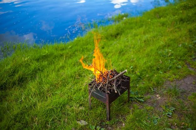 Brandend vuur met vlammen in een draagbare bbq buiten op een groen gazon in de buurt van de rivier in de zomer. een kleine opvouwbare draagbare vuurpot gevuld met brandend hout. koken op de grill. veilig vuur in de natuur.