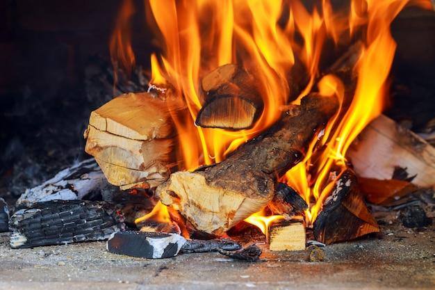 Brandende en gloeiende stukken hout in openhaard