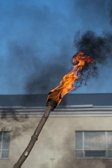 Brandende fakkel en zwarte rook tegen de blauwe lucht