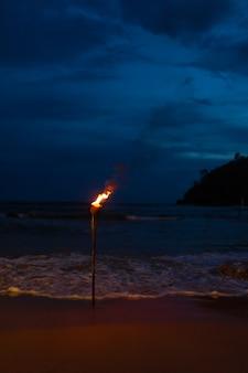 Brandende fakkel op het zandstrand van de oceaan