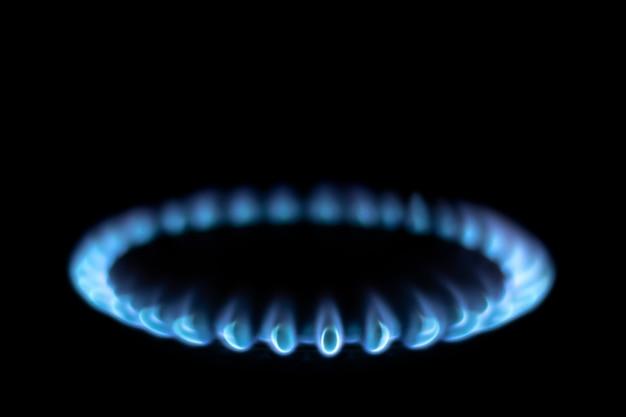 Brandende gasfornuis brander blauwe vlam op een zwarte achtergrond. blauw gas in het donker
