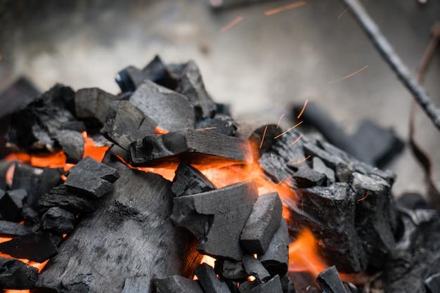 Brandende houtskoolclose-up. kolen in vuur en rook.