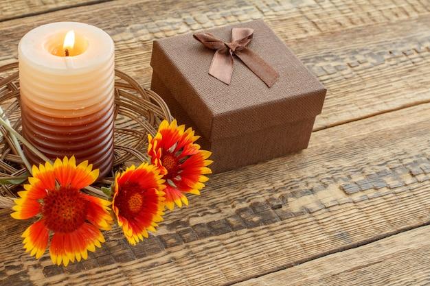 Brandende kaars, bruine geschenkdoos verpakt in kraftpapier met rood lint en bloemen op houten planken. bovenaanzicht. vakantieconcept.