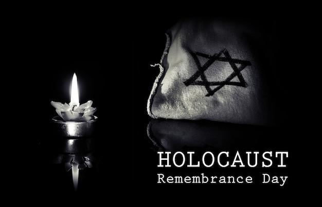 Brandende kaars en de davidster tegen een zwarte achtergrond, we zullen nooit vergeten, de joodse holocaust en heldhaftigheid. holocaustherdenkingsdag 27 januari