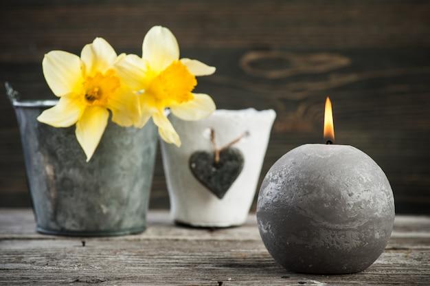 Brandende kaars en gele bloemen