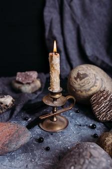 Brandende kaars en stenen op het heksentafel occult esoterisch concept