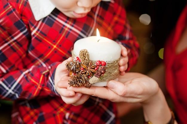 Brandende kaars in de handen van moeder en klein meisje. kerst decor. moeder en kind met mooie kaars met vuur. kersttijd. gelukkig gezin.