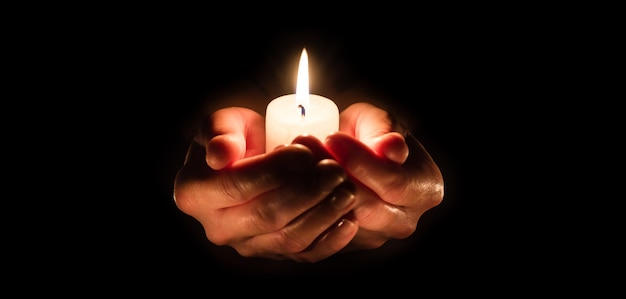 Brandende kaars in vrouw overhandigt zwart. religieus kerst spa en wellness concept - kopieer ruimte.