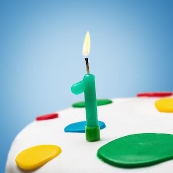 Brandende kaars met nummer één op een verjaardagstaart