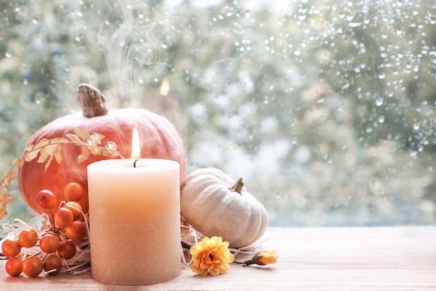 Brandende kaars, pompoen en herfst decoraties op een raam