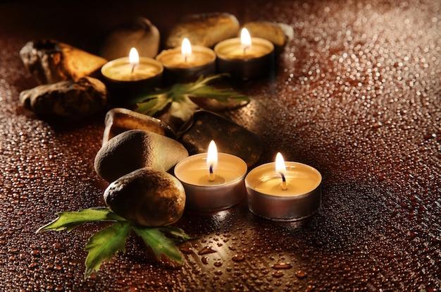 Brandende kaarsen en druppels water. steen therapie. spa behandelingen.