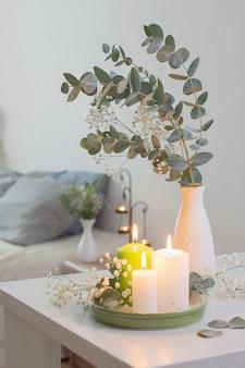 Brandende kaarsen en eucalyptus in vaas in witte slaapkamer