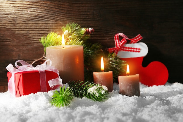 Brandende kaarsen en kerstaccessoires met sneeuw op houten tafel