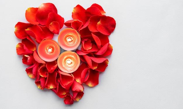 Brandende kaarsen en rozenblaadjes in de vorm van een hart