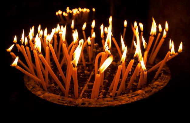 Brandende kaarsen in een kerk op een donkere ondergrond