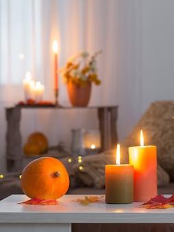 Brandende kaarsen met herfstdecor op witte tafel thuis