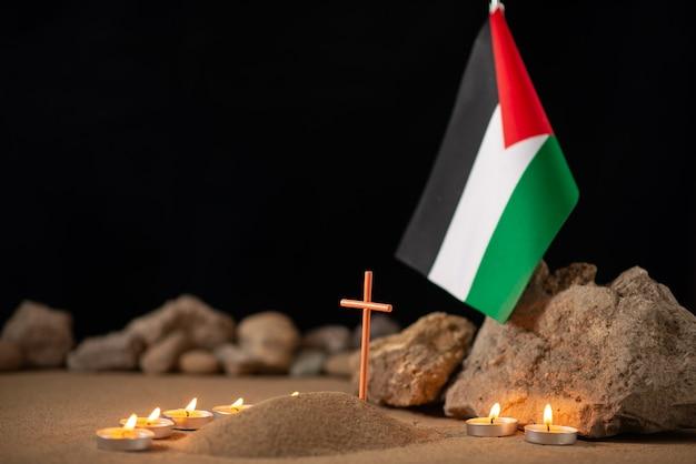 Brandende kaarsen met palestijnse vlag rond klein graf