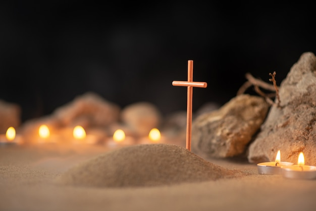 Brandende kaarsen met stenen rond grafje als herinnering aan begrafenissterfte