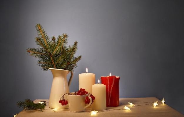 Brandende kaarsen op tafel, groene spar staat in een witte vaas