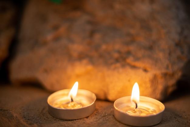 Brandende kaarsen op zand als herinnering aan begrafenissterfte