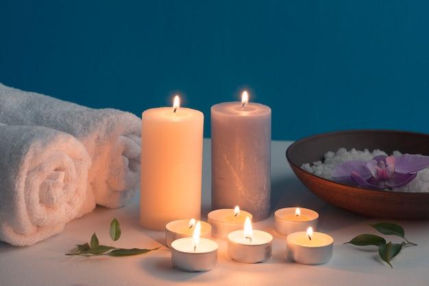 Brandende kaarsen, opgerolde handdoek en bath spa zout op tafel