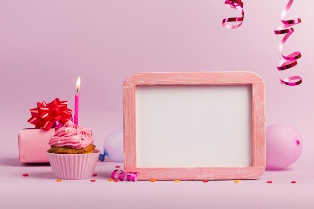 Brandende kaarsen over de muffins met witte kaderlei op roze achtergrond