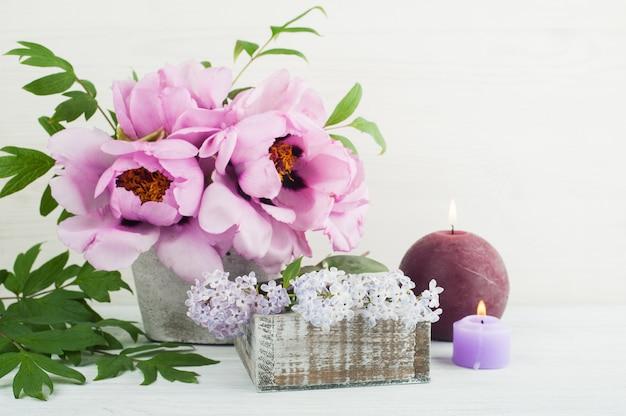 Brandende kaarsen, pioenrozen en lila bloemen