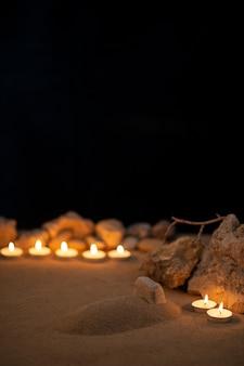 Brandende kaarsen rond klein graf als herinnering op donkere ondergrond