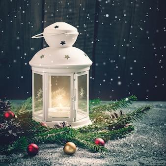 Brandende kaarslantaarn en kerstsamenstelling van vuren takken en ballen.