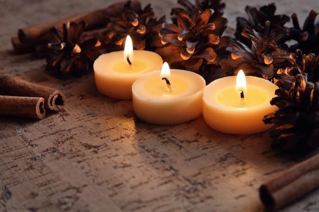 Brandende kerst kaarsen versierd met dennenappels