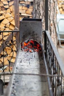 Brandende kolen in een metalen grill voor het braden van vlees en groenten. koken op een kampvuur.