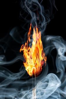 Brandende lucifer met de rook op zwart