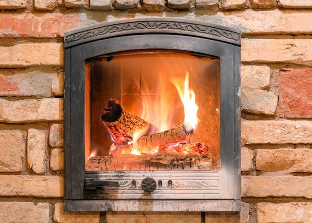 Brandende open haard met houten blokken en vlammen binnen.