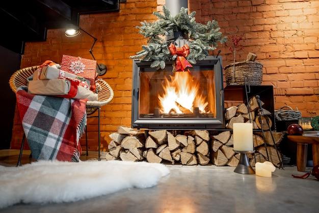 Brandende open haard versierd met een cadeautje en een nieuwjaarskrans in een gezellig interieur