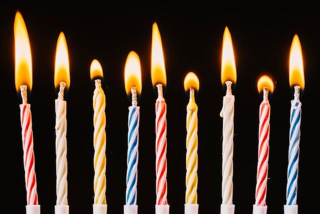 Brandende verjaardagskaarsen op zwarte achtergrond