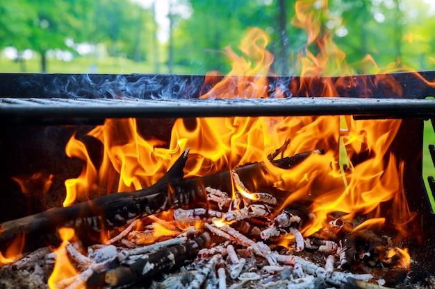Brandende vlammen en gloeiende kolen in bbq, warm oranje vreugdevuur met stukken hout