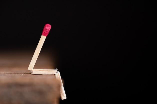 Brandende wedstrijd menselijke zittend op houten tafel op een donkere achtergrond.