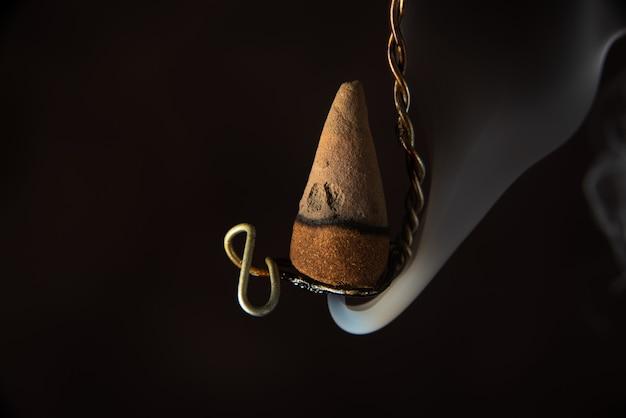 Brandende wierook opknoping op een oude draad, selectieve aandacht.