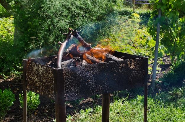 Brandhout branden in de barbecue. vreugdevuur voor een picknick. zonnige zomerdag buitenshuis.