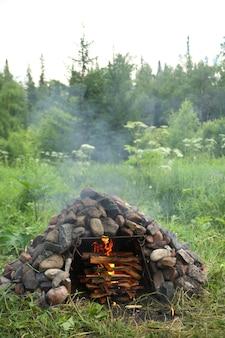 Brandhout branden in kachel gebouwd van grote stenen buiten in het bos